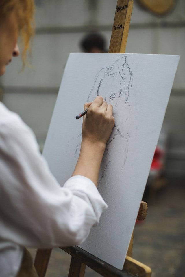 woman-in-white-long-sleeve-shirt-drawing-on-paper-3778179.jpg
