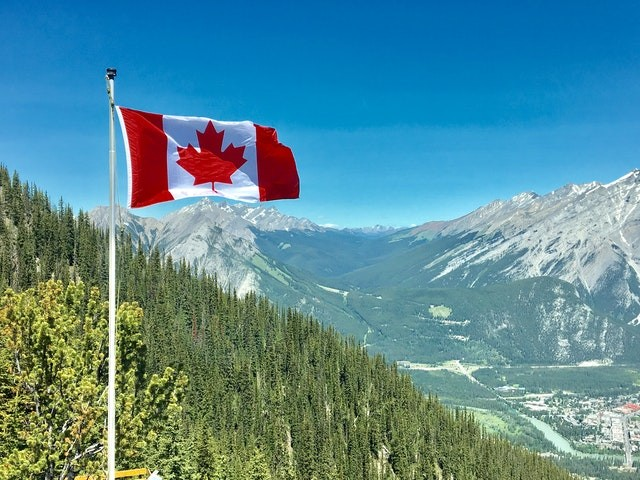 canada-flag-with-mountain-range-view-756790.jpg